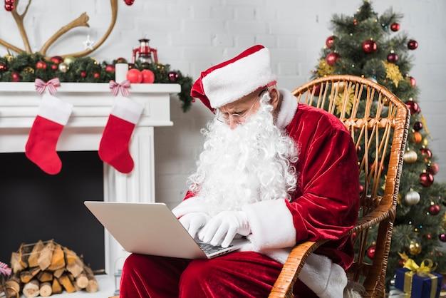 Санта, сидя на качалке и набрав на ноутбуке
