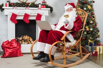 Santa sitting on rocking chair with laptop