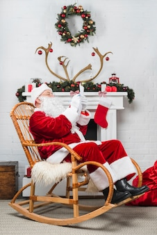 Santa sitting in rocker with wishlist