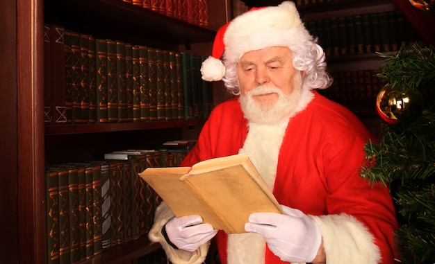 Santa standing at the christmas tree and reading a book.