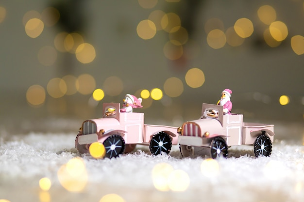 Santa statuette rides on a toy car with a trailer for gifts