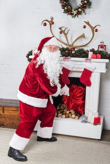 Santa with big sack getting into house