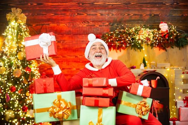 크리스마스 선물을 든 산타 크리스마스 선물을 들고 실내에 있는 재미있는 산타 남자의 초상화 수염난 남자가 데...