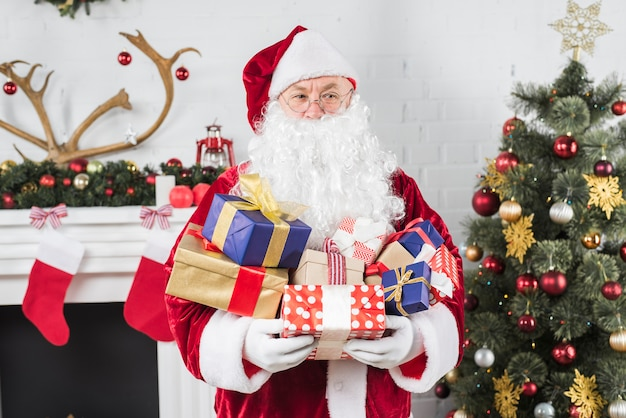 Santa with gift boxes in hands near christmas tree