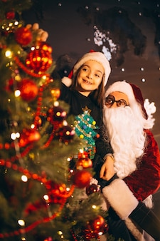 Santa with little girl decorating christmas tree together
