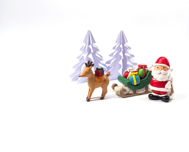 Santa  with sleighl full of gists in front of origami christmas tree ,  waiting for the festival of happiness