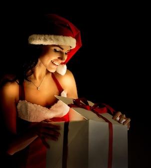 마법의 크리스마스 선물 상자를 여는 산타 여자