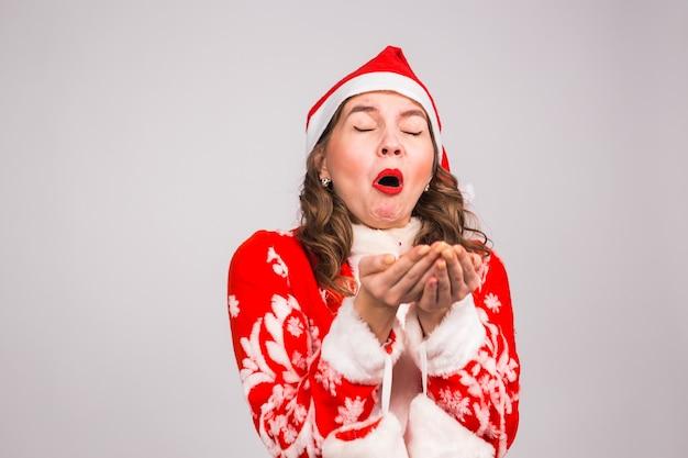Santa woman sneezing on white wall.
