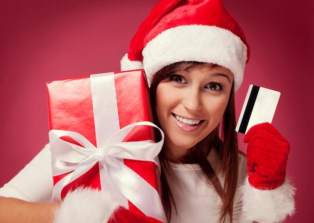 赤いギフトボックスとクレジットカードを持つサンタの女性