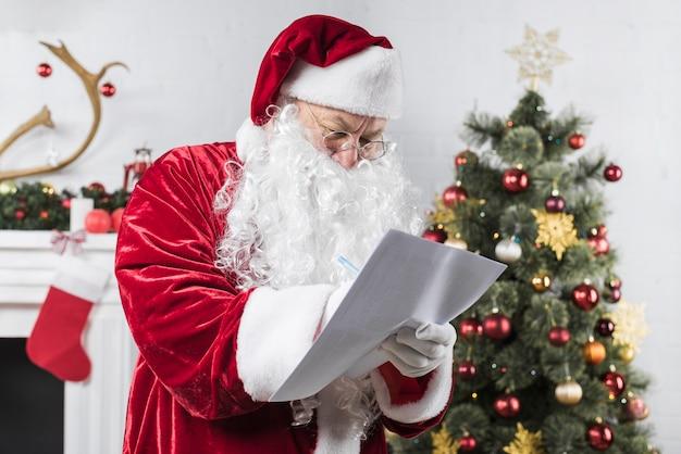 Santa writing on paper near decorated christmas tree