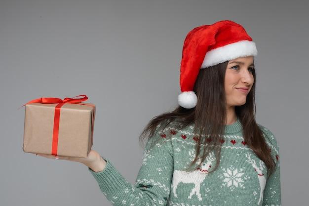 暖かい冬のセーターとクリスマスの新年の贈り物と赤い帽子のサンタの若い女の子
