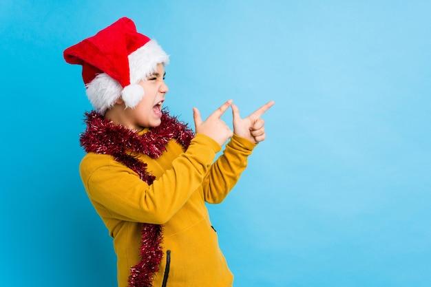 Мальчик празднуя рождество нося шляпу santa изолировал указывать с указательными пальцами к космосу экземпляра, выражая ободрение и желание.