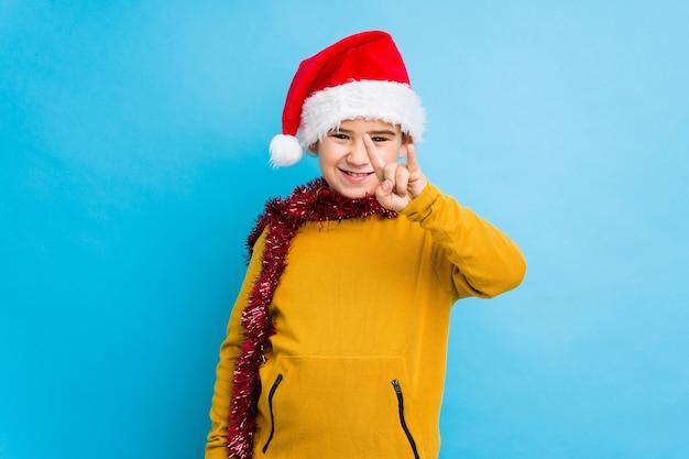 Мальчик празднуя рождество нося шляпу santa изолировал показывать жест рожков как концепция революции.