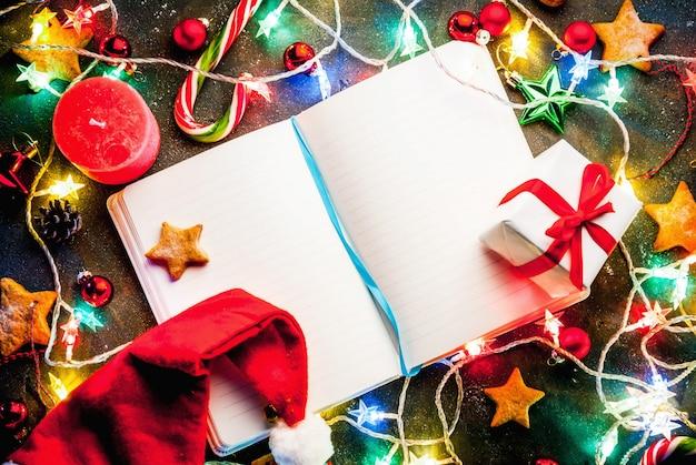 Поверхность рождества темная с гирляндой рождества, украшениями, звездами пряника, подарочной коробкой и шляпой и свечами santa. копия сверху, с блокнотом для желающих