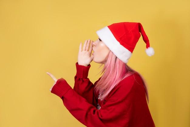 Спрашивая девушка с красным костюмом santa