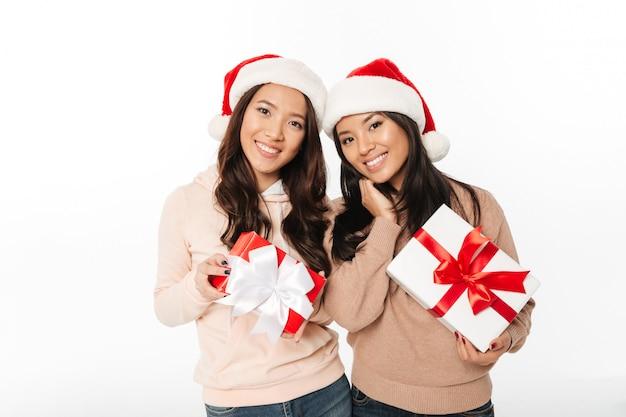 Азиатские милые сестры повелительниц нося шлемы рождества santa