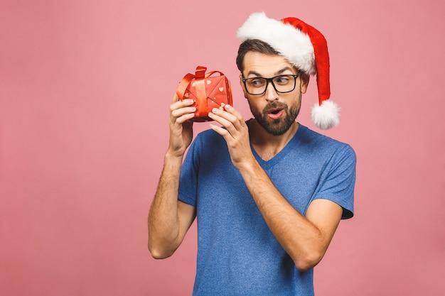 Изображение счастливого молодого человека нося положение шляпы santa рождества изолированное над розовой стеной держа коробку подарков.