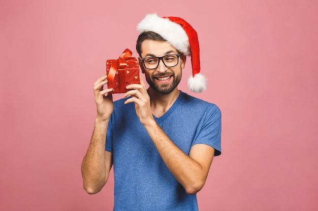 Изображение счастливого молодого человека нося положение шляпы santa рождества изолированное над розовой стеной держа подарочную коробку.