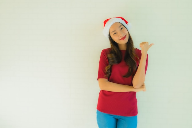 Женщины портрета красивые молодые азиатские нося шляпу santa для торжества в рождестве