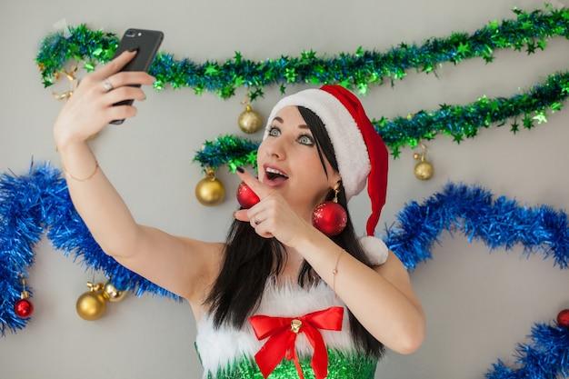 그녀의 손에 전화와 엘프 의상 산타의 섹시 도우미 열정적 인 갈색 머리