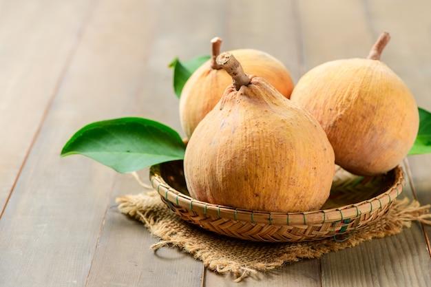 Плоды сантола в бамбуковой корзине на деревянном фоне,