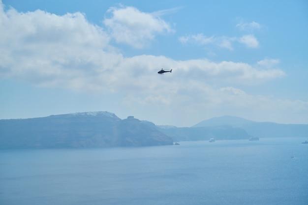 サントリーニ島と海上空のヘリコプター