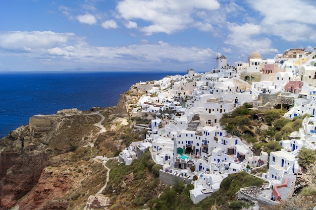 Santorini island, greece. traditional and famous houses and churches with blue domes over the caldera, aegean sea