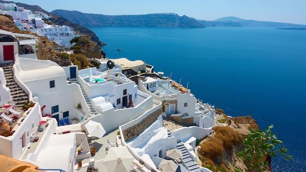 Остров санторини в греции. панорамный вид городка ия белые домики у моря. греческий пейзаж