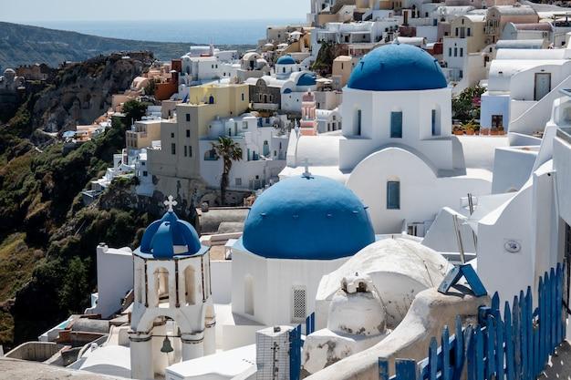Деревня santorini oia церков 3 голубых куполов в острове santorini, греции.
