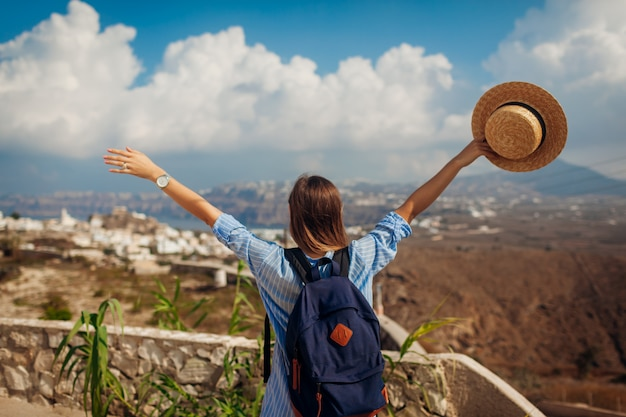 Santorini traveler with backpack raised arms feeling happy looking at akrotiri, mountains landscape on island. tourism