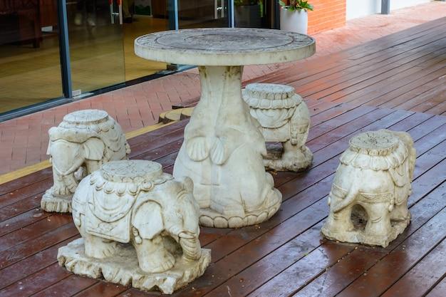 싼야, 하이난, 중국 - 2020년 2월 20일: 불교 중심지 난산의 영토에 작은 코끼리 형태의 의자가 있는 돌 탁자.