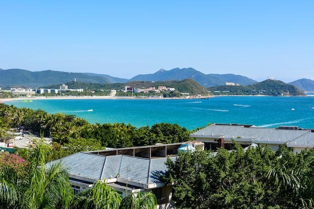 中国海南省三亜-2020年2月20日:ホテルから南シナ海の大東海湾の海岸にあるターコイズブルーの海、山、ビーチ、ジェットスキー、モーターボート、パラシュートを一望できます。晴れた日