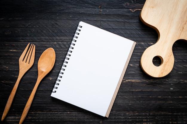 コピーsapceと木製の表面上のテキストのメモのための空白のノートブック