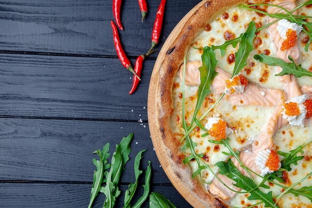 Пицца взгляд сверху с семгами, рукколой, красной икрой, сыром на темной деревянной предпосылке с sapce экземпляра. итальянская пицца с морепродуктами. продовольственный фон. вкусная домашняя пицца итальянской кухни