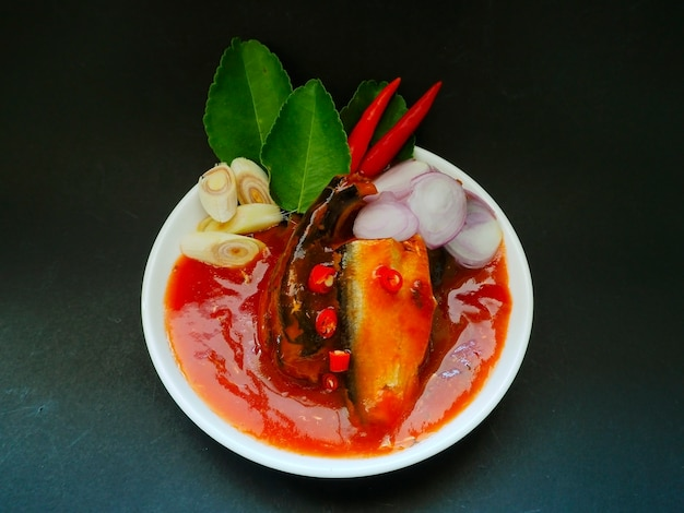 Сардины в томатном соусе на темном фоне табло