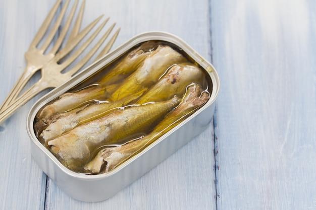 Sardines in iron box on blue wooden