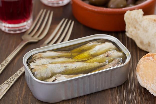 Sardines in iron box on brown wooden