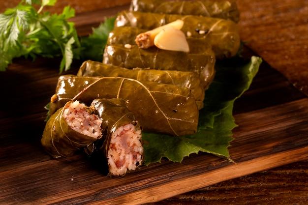 Сарма - рис и мята, завернутые в листья виноградной лозы на деревянном фоне.
