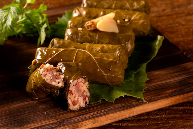 Sarma - rice and mint wrapped in grape vine leaves on wood background.