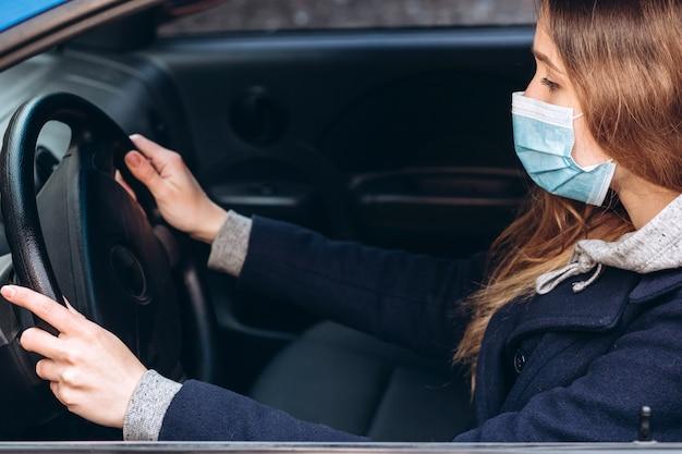 車の中で医療マスクの少女のポートレート、クローズアップ。コロナウイルスエピデミック。パンデミックでの街中の動き。女性は自己分離のルールに違反しました。 sars-cov-2。 covid-19を停止します。