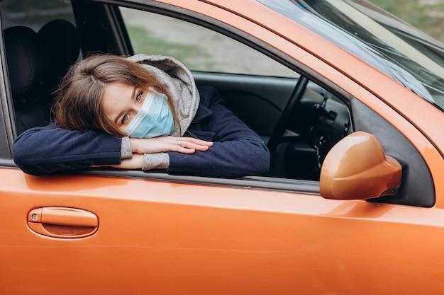 車の中で医療マスクの女性のポートレート、クローズアップ。コロナウイルスエピデミック。 sars-cov-2。 covid-19を停止します。
