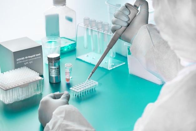 新規コロナウイルス検出:sars-cov-2検出用のpcrキットと、回復した患者の血液中のウイルスに対する抗体を検出するための迅速なキット。疫学者はテストラボで働いています。