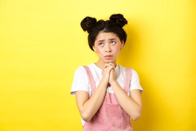 Sas asian girl holding hands in pray, pleading god, looking up and begging, standing on yellow.