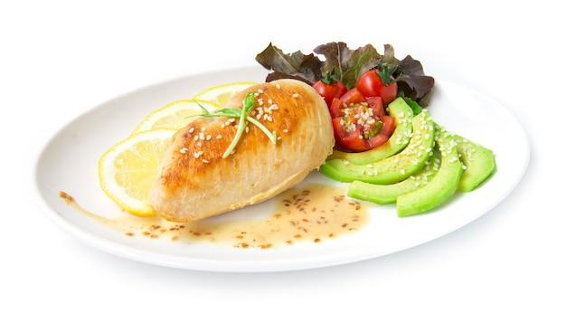 グリルした鶏の胸肉または鶏肉のステーキをsasemiソースフュージョンフードモミダイエットと健康的な彫刻が施されたトマトとアボカドスライスリーフレッドオークサイドビューは、白い背景で隔離