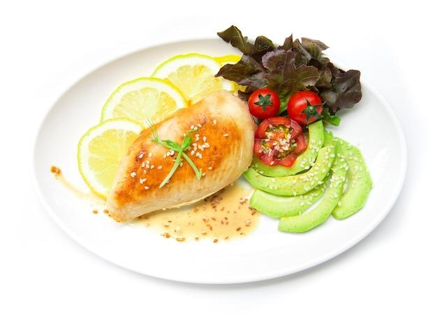 グリルした鶏の胸肉または鶏肉のステーキをsasemiソースフュージョンフードモミダイエットと健康的な彫刻が施されたトマトとアボカドスライスリーフレッドオークトップビューで孤立した白い背景