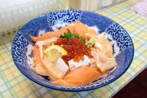 青いボウルにイクラとご飯を入れた刺身生魚