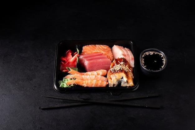 Набор сашими из лосося, креветок, тунца и угря в черном пластиковом контейнере на темном фоне