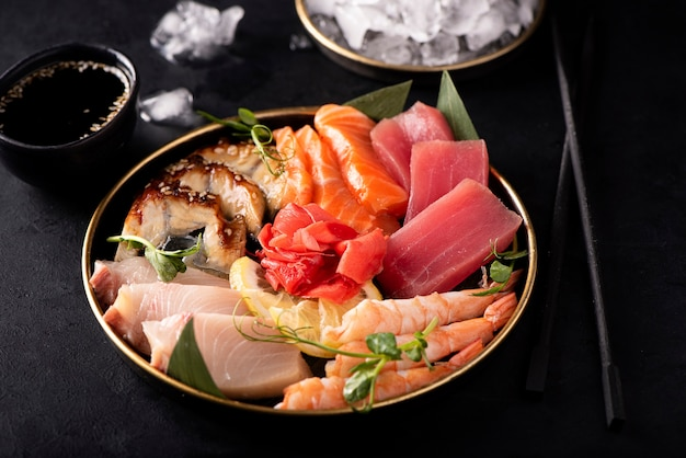 Набор сашими из лосося, креветок, тунца и угря на черной тарелке