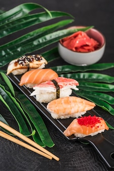 Sashimi sushi set with chopsticks and ginger on a dark surface