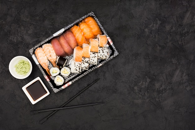 Sashimi sushi set with soy and wasabi on black background
